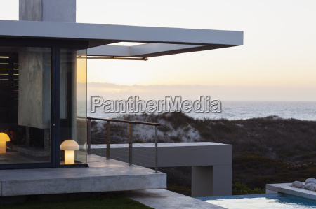 modern house overlooking ocean at sunset