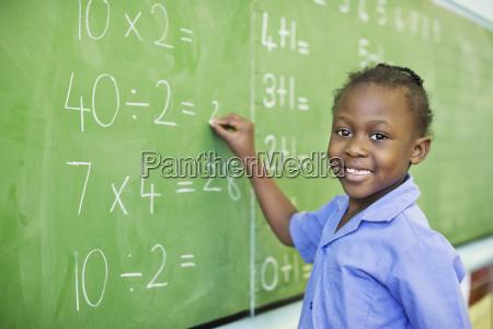 student writing on blackboard in class