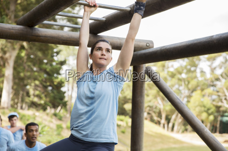 determined woman crossing monkey bars on