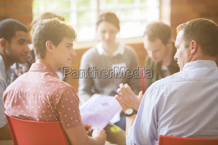 men talking in group therapy session