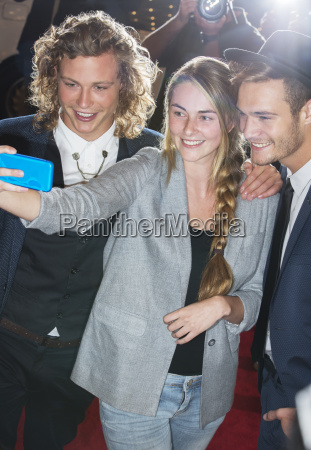 fan taking selfie with celebrities at