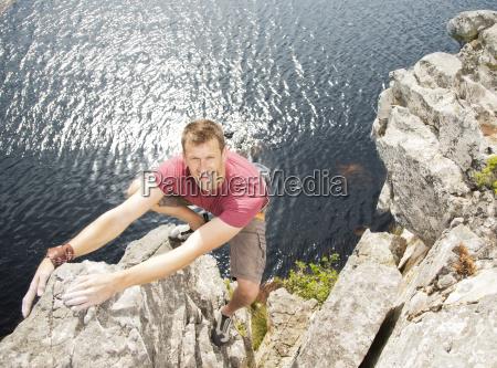climber scaling coastal cliff