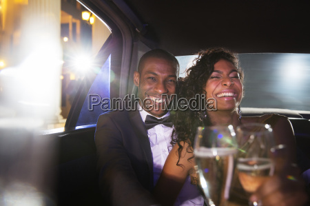 laughing celebrity couple drinking champagne inside