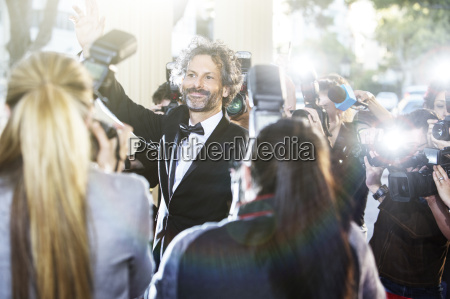 celebrity waving at paparazzi photographers at