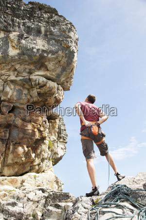 climber examining rock formation