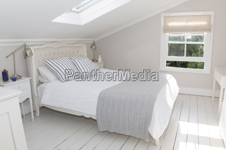 bed in whitewashed attic bedroom