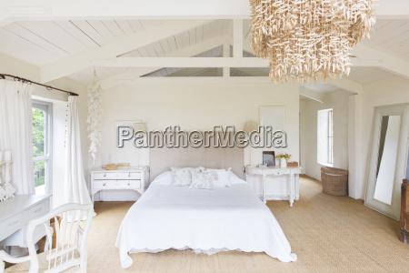 chandelier and bed in rustic bedroom