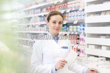 portrait of confident pharmacist holding prescription