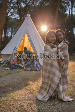 children wrapped in blanket at campsite