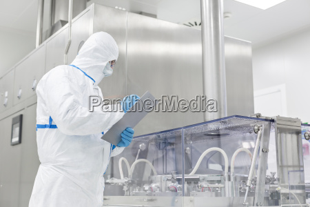 scientist in clean suit writing on