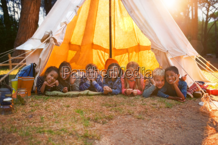 children smiling in teepee at campsite