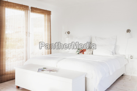 bed and bench in white bedroom