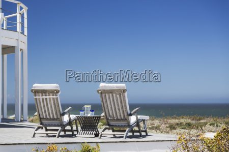 lounge chairs on patio overlooking ocean