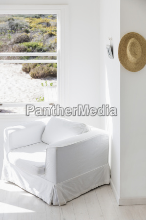armchair next to window overlooking beach