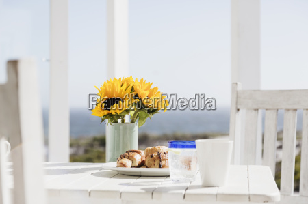sunflowers and croissants on patio table