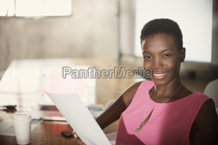 portrait smiling businesswoman with paperwork in