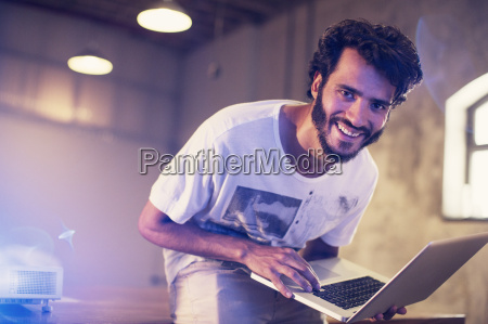 portrait enthusiastic casual businessman with laptop