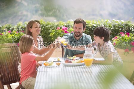 family toasting orange juice glasses at