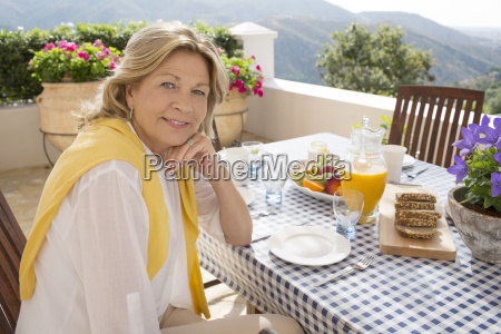 senior woman eating breakfast at table