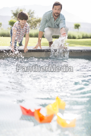 father and son racing paper boats