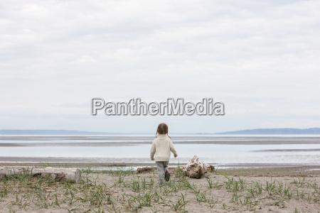 girl running toward ocean on beach