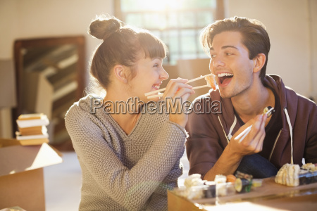 couple eating sushi together in new