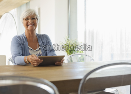 older woman using tablet computer at