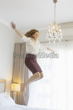 businesswoman jumping on bed in hotel