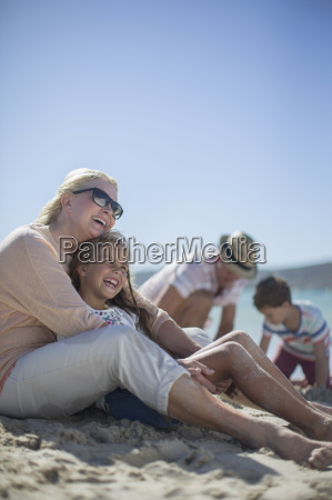 family sitting together on sandy beach