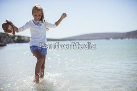 young girl splashing in water on