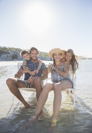 family sitting in chairs in waves