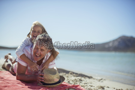 grandfather and granddaughter playing on beach
