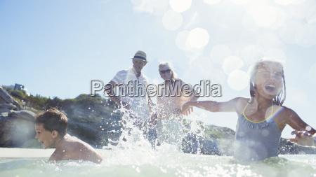 family splashing each other on beach