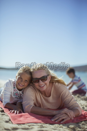 grandmother and granddaughter laying on beach