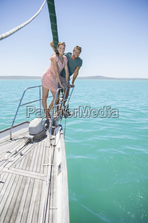couple standing on front of sailboat