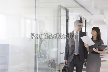 businessman and businesswoman discussing report in