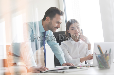 businessman and businesswoman working at laptop