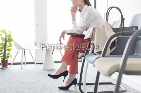 businesswoman waiting with legs crossed in