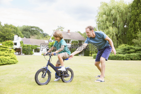 father pushing son on bicycle in