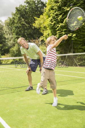 father and son playing tennis on