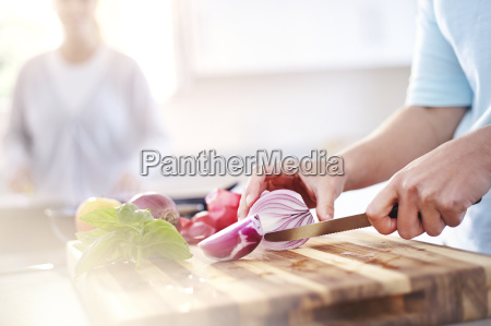 woman slicing red onion on cutting