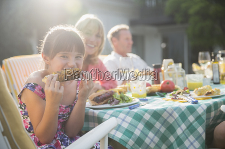 girl eating corncob at table in