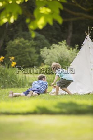 father and son laying outside teepee