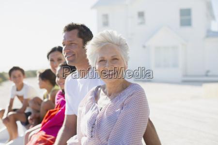 multi generation family smiling outside beach