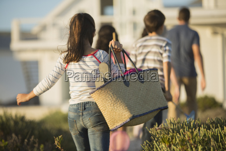 girl with beach bag following family