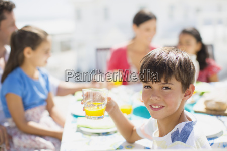 boy drinking juice at table on