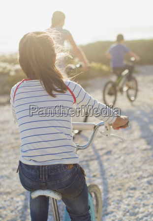 family riding bicycles on sunny beach