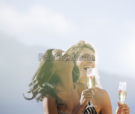 women drinking champagne together outdoors