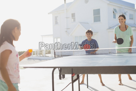 family playing table tennis together outside