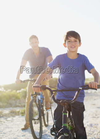 father and son riding bicycles on